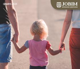 Criança andando de mãos dadas com os pais