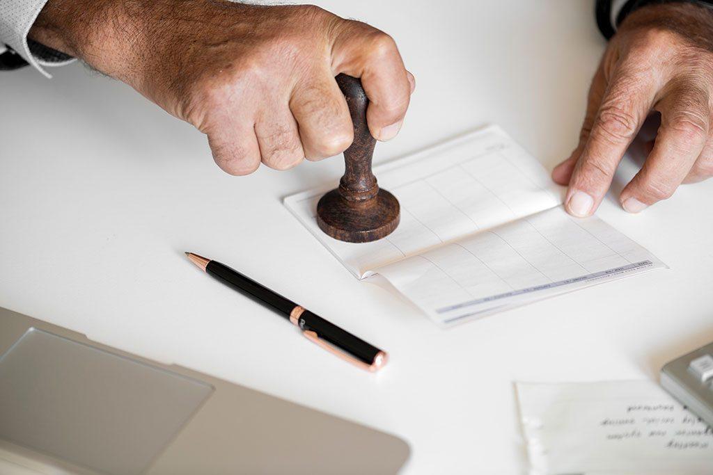 Pessoa carimbando marca registrada em documento oficial
