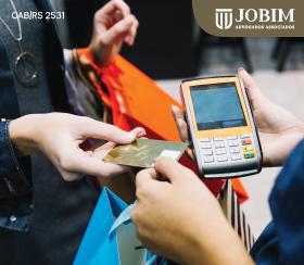 Comerciante e consumidor efetuam pagamento no cartão de crédito em loja