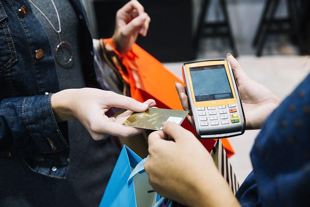 Comerciante e consumidor efetuam pagamento em cartão de crédito em loja